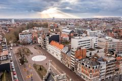 Солнечные лучи выходя сквозь отверстие вершина облака, с панорамой лёвена, Фландрия, Бельгия стоковое фото