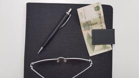 Солнечные очки около черной ручки и одной китайской банкноты денег стоковое фото rf