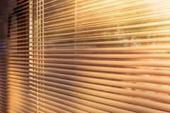 Солнечный свет утра на восходе солнца светя через предкрылки горизонтальных венецианских шторок стоковое фото rf