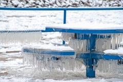 Сосульки на голубых скамейке в парке и таблице стоковые изображения rf