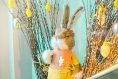 Состав пасхи с кроликом и яйцами игрушки вися на букете pussy-вербы на голубой предпосылке стоковое фото