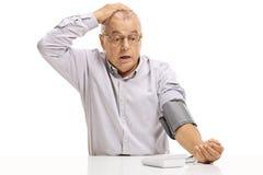 Сотрясенный зрелый человек принимая измерение кровяного давления стоковая фотография