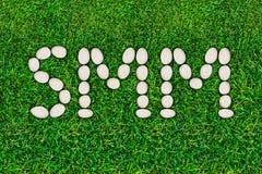 Социальные средства массовой информации выходя SMM вышед на рынок на рынок Письма положенные из камней реки на зеленую траву прик стоковое изображение rf