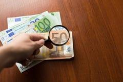 Сохранение, налог или ища финансов для концепции выхода, стекла увеличителя на куче банкнот евро на деревянном столе, прозрачност стоковая фотография rf