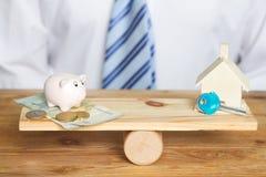 Сохранение для концепции дома и баланса с деньгами и копилкой на качании стоковая фотография rf