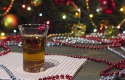 Coñac en un vidrio, ornamentos de la Navidad y árbol de navidad Imagen de archivo libre de regalías