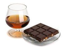 Coñac y chocolate en un platillo de cristal Foto de archivo libre de regalías