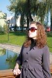 Coûts de fille sur la passerelle en glaces de soleil Photo stock