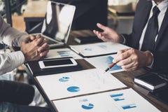 Co工作会议,企业队会议礼物,谈论投资者的同事新的在办公室桌上的计划财政图表数据 免版税库存照片