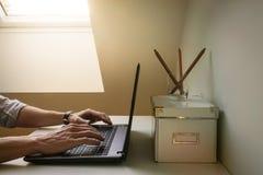 一个人研究手提电脑在 co的一个天窗窗口下 库存照片