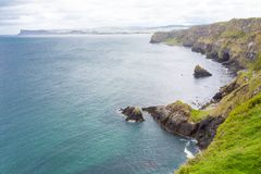 Co. Antrim`s Rolling Hills. Co. Antrim, N. Ireland/United Kingdom - June 2, 2015: On the north coast of northern Ireland in County Antrim the North Sea sparkles royalty free stock images