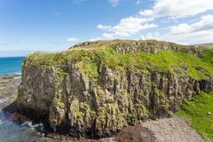 Co. Antrim`s Rolling Hills. Co. Antrim, N. Ireland/United Kingdom - June 2, 2015: On the north coast of northern Ireland in County Antrim the North Sea sparkles royalty free stock image