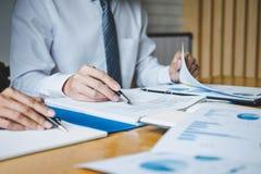 Co-arbetekonferens, ut?vande lag som diskuterar diagrammen och graferna som arbetar i aff?rsstrategi och finansiellt plan till arkivbild