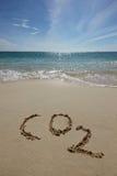 CO2 on a beach. CO2 handwritten in sand on a tropical beach Royalty Free Stock Photos
