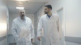 Co-doutores que andam no hospital, no conselho e na enfermeira vindo para a ajuda 4K filme