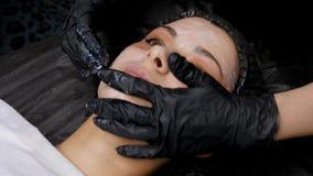 CO2 fraccionario del laser Procedimiento cosm?tico Aplique la crema analgésica a la cara antes del procedimiento Mujer que tiene  almacen de metraje de vídeo