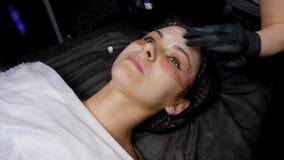 CO2 fraccionario del laser Procedimiento cosm?tico Aplique la crema analg?sica a la cara antes del procedimiento Mujer que tiene  metrajes