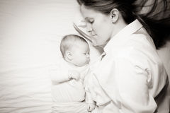Co-sleeping mother and baby. Co-sleeping mother and three months baby after breastfeeding on the bed Royalty Free Stock Image