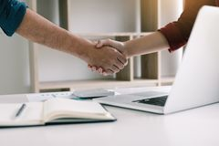 Co-worker startup shaking hands with colleagues in home office.  stock photo
