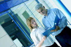 Co-Workers Collaborating. Two casually dressed business people look over a folder with documents regarding an important project on which they are working.  Color Stock Photos