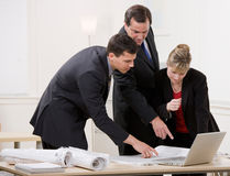 Co-workers collaborating on blueprints Stock Photos