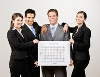 Co-workers holding financial line graph Stock Photo