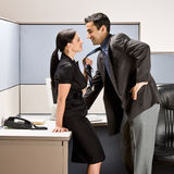 Co-workers kissing in office cubicle. Co-workers flirting in an office cubicle Royalty Free Stock Photos