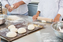 Co-workers kneading uncooked dough together Stock Photos