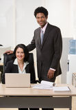 Co-workers with laptop at desk Royalty Free Stock Photo