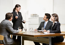 Co-workers listening to supervisor Royalty Free Stock Photos