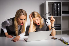 Co-workers looking at computer in shock Royalty Free Stock Images