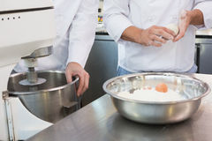 Co-workers making dough with eggs and flour Stock Image