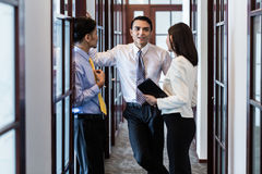 Co-workers in office hallway talk about project stock images