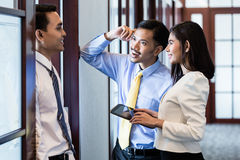 Co-workers in office hallway talk about project royalty free stock images