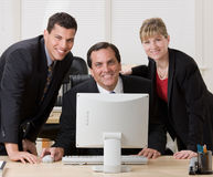 Co-workers posing together at desk Stock Photo