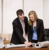 Co-workers review blueprints at desk Royalty Free Stock Photo