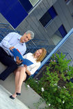Co-Workers Review A Project-2. Two co-workers casually sit outside of a large office building on a concrete curb and review the final documents in a folder of Stock Photography