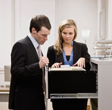 Co-workers searching through file drawers Royalty Free Stock Photos