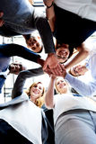 Co-workers standing in circle looking down Royalty Free Stock Photo