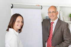 Co-workers standing next to flipchart Royalty Free Stock Image