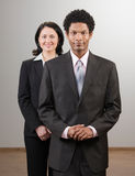Co-workers in suits posing Royalty Free Stock Images