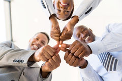 Co-workers thumbs joined Stock Photos