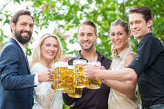 Co-Workers after work drinking beer together Stock Photography