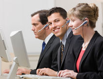 Co-workers working at computers in call center. Happy co-workers in headsets working at computers in call center Royalty Free Stock Images