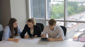Co-working people are discussing documents sitting in office. stock video footage