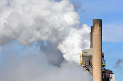 CO2 emissions and industrial smokestacks. Factory smokestacks pumping pollution and carbon into the atmosphere royalty free stock photography
