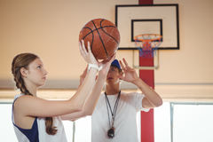 Coach advising female basketball player. While practicing in court Royalty Free Stock Photo