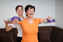 Coach assisting senior woman exercising Royalty Free Stock Images