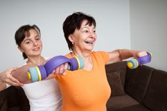 Coach assisting senior woman exercising. Smiling senior fitness women exercising with barbells assisted by coach Royalty Free Stock Image