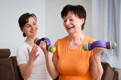 Coach assisting senior woman exercising Royalty Free Stock Photo